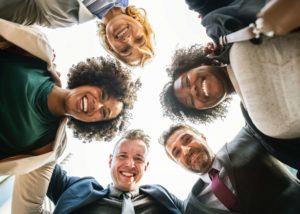 Eine Gruppe von Menschen steht zusammen und legt den gemeinsamen Fokus der Arbeit auf Kreativität und Selbstverwirklichung.